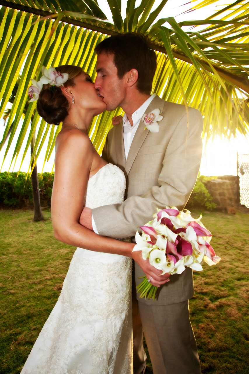 first kiss bride and groom under palm leaf