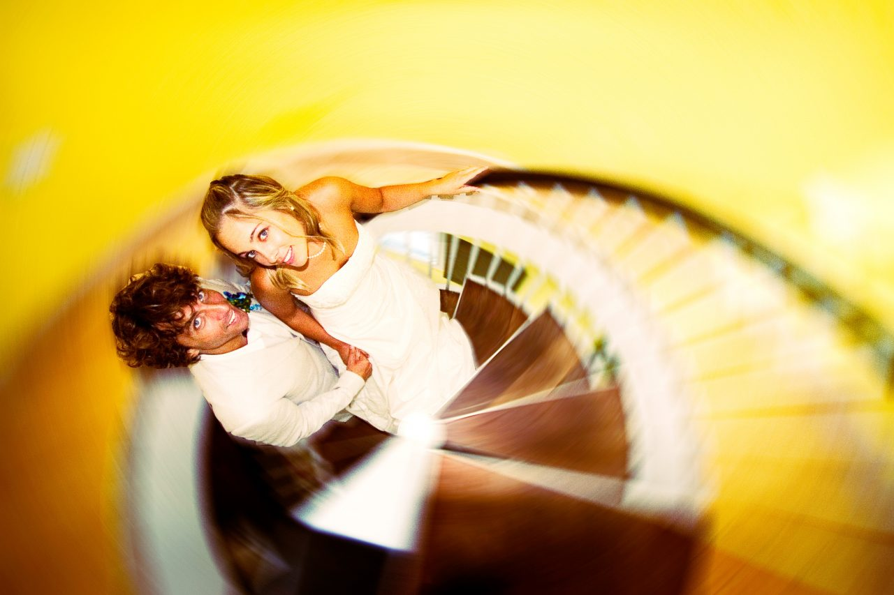 bride and groom pose on spiral staircase